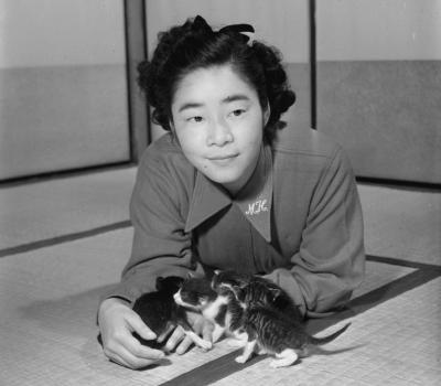 タマのモデル?の猫とたわむれる長谷川町子さん。サザエさんは「猫は魚好き」というイメージを決定づけた=1951年