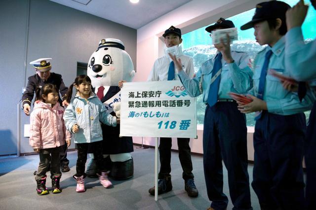 118番を知ってもらおうと、リーフレットを配る青森海洋少年団のメンバーら=青森市の県営浅虫水族館