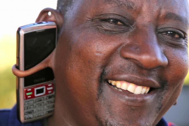耳たぶの穴に携帯電話を挟んで手放しで会話をするマサイ族の男性=2014年12月
