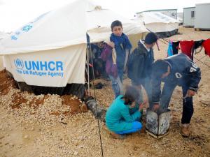 ヨルダン・ザアタリ難民キャンプで、テントの外でオリーブの枯れ枝を燃やして暖をとる子供たち=2013年12月13日、松尾一郎撮影