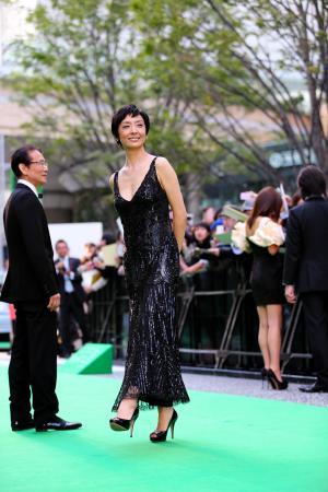 東京国際映画祭のグリーンカーペットを歩く俳優の草刈民代さん(中央)と夫の周防正行監督(左)。草刈さんは、映画「終の信託」で「クラシコ」の白衣を着用=2012年10月