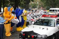 出動するパトカーを見送る警察のマスコットたち。周りの景色が映り込むくらいピカピカのパトカー=2010年9月、東京・霞が関の警視庁
