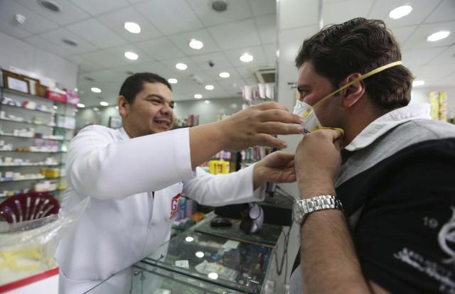サウジアラビアのタイフの薬局で、購入したマスクを着用する男性客=2014年11月、ロイター