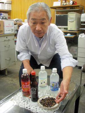 北海道民におなじみの「ガラナ」飲料を前に、ガラナの実を手にする小原光一社長=2011年10月