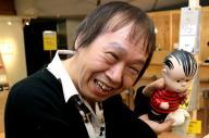 スヌーピー展会場のショップでフィギュアを手にする祖父江慎さん=2013年10月、東京都港区