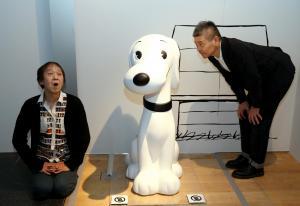 展示の最後にあるスヌーピーの大きなフィギュアと祖父江さん(左)、糸井さん=2013年10月、東京都港区