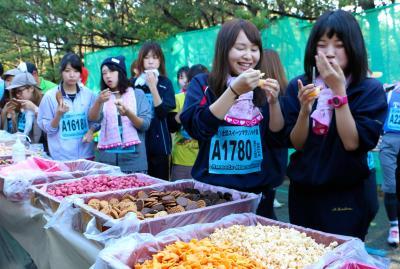 もはやランニングをこえたイベント?給水所でお菓子が食べられる「スイーツラン」=2014年11月、千葉市の稲毛海浜公園