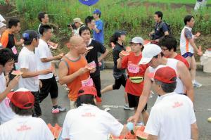 スイカを楽しみながら走る富里スイカロードレース大会の「給スイカ」。レースそっちのけでスイカを楽しむ参加者=千葉県富里市内