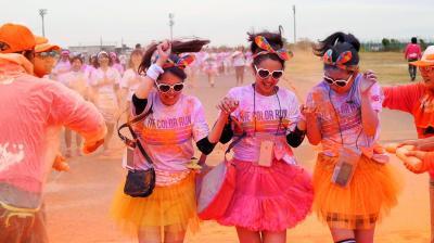 カラーランに参加した女性3人組は「オーレンジ! オーレンジ!」と叫びながら小走りでパウダーを浴びた=2014年11月、大阪市此花区の舞洲スポーツアイランド
