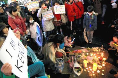 後藤健二さんと湯川遥菜さんの追悼集会で、ろうそくや花束を供える人たち=2015年2月8日
