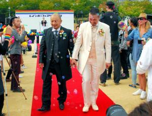 式を終え、来場者から祝福される男性カップル