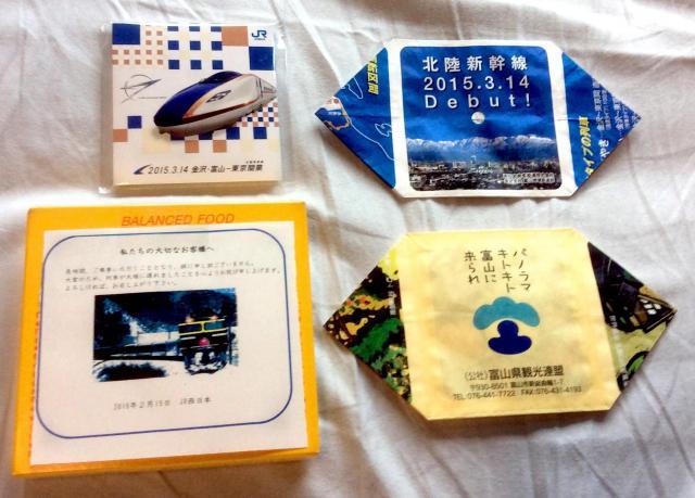 車内で乗客に配られたメッセージカード付きの栄養補助食品や北陸新幹線の紙風船など