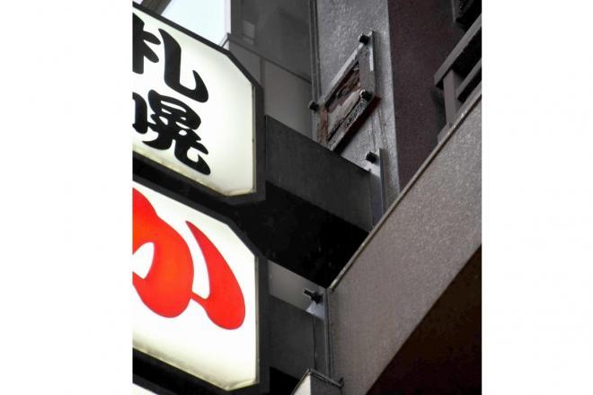落下した看板の取り付け部分(中央上部)=15日午後4時41分、札幌市中央区、恵原弘太郎撮影