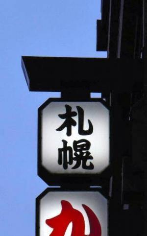 ビルの別の場所に取り付けられている同様の看板。最上部が落下した=札幌市中央区、恵原弘太郎撮影