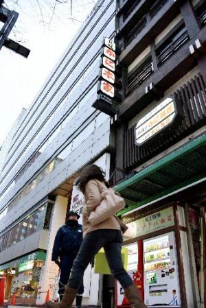 看板の一部が落下したビルの下では警察官が立ち、歩行者に注意を促していた=2月15日、札幌市中央区、恵原弘太郎撮影