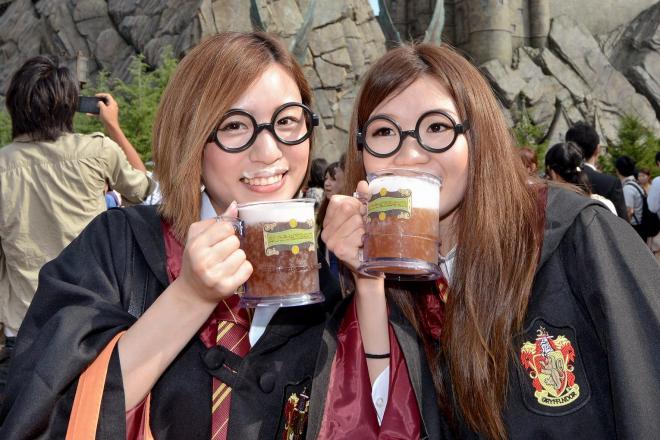 シンボルの「ホグワーツ城」前で魔法界の名物「バタービール」を飲む人たち=2014年7月15日、大阪市此花区、竹花徹朗撮影