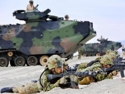日米合同の離島奪還訓練で砂浜に上陸した米海兵隊の水陸両用車AAV7から降り、周辺を警戒する陸自隊員=米海兵隊ペンドルトン基地、福井悠介撮影