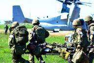 戦闘中に銃撃を腹に受けたり片足を切断したりした想定の下、米海兵隊の新型輸送機オスプレイに運ばれる陸自隊員=米カリフォルニア州のペンドルトン基地