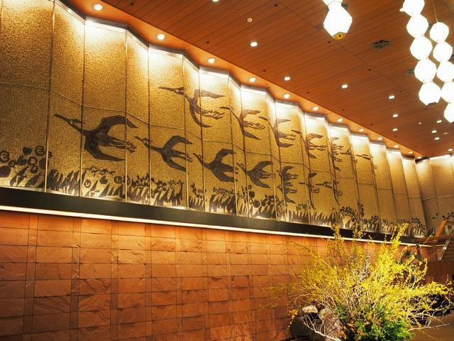 別館ロビー。棟方志功原作「鷺畷の柵」を白黒の陶板タイルで制作したモザイク画で、横30m×縦4mある。下の壁はインド砂岩。天井のライトはアトランダムに配置され、やわらかい光になっている