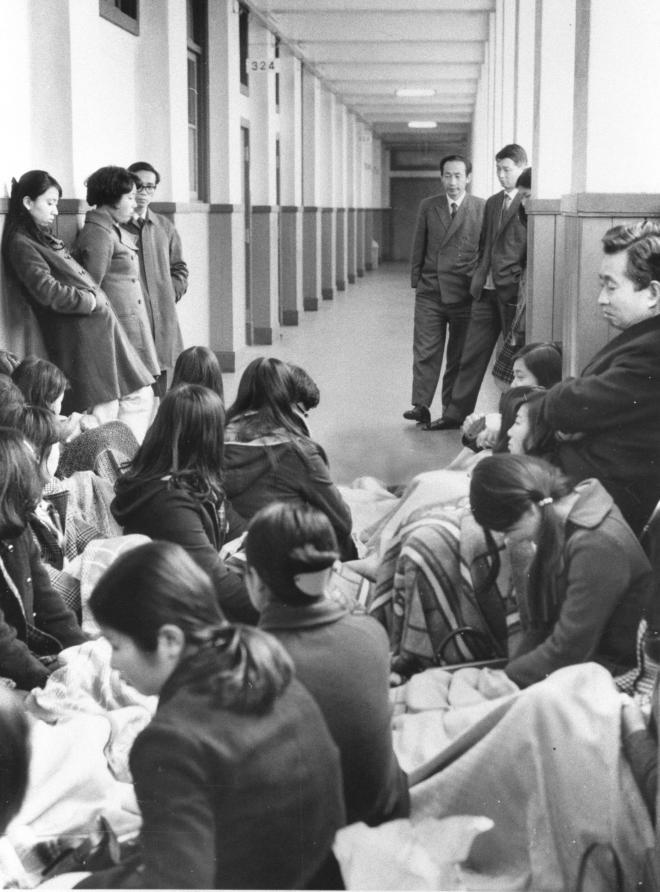 (6)学生自治会役員の処分をめぐって紛争が続いている国立図書館短期大学(今の筑波大学)で、学生がつけていた処分に抗議するゼッケンを河野通教授がはぎ取ったとして、廊下で河野教授(右端)に陳謝を要求する学生たち=1971年2月21日