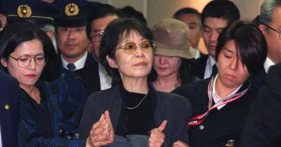 捜査員に囲まれる重信房子受刑者(中央)=2000年11月7日