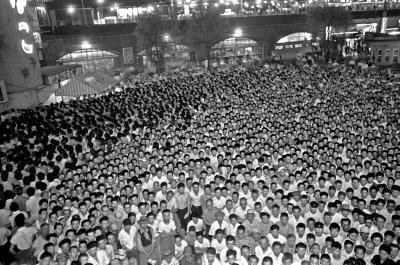 街頭テレビでの力道山の試合中継に見入るファンたち。東京・新橋駅西口広場には、1万2千人が群がった=1955年7月0日