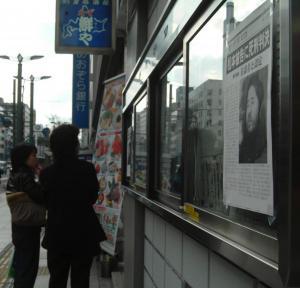 松本智津夫死刑囚の死刑判決を伝える新聞の速報に見入る人たち=2004年2月27日、広島市中区