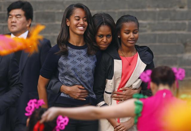 娘のマリア(左)とサーシャ(右)を抱きしめるミシェル夫人=2014年3月24日