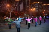 夜の駐車場で踊る広場舞のグループ。周囲には多くのマンションが立ち並ぶ=1月下旬、山東省・済南市、延与光貞撮影