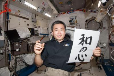 書初めで書いた「和の心」を手にもつ若田宇宙飛行士、2014年1月1日=JAXA/NASA