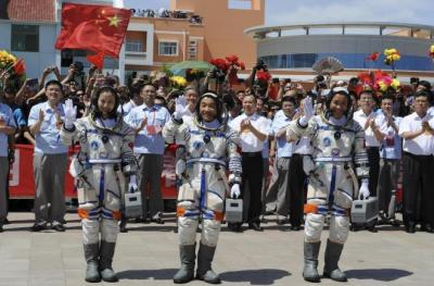 中国の衛星発射センターを出発して手を振る宇宙飛行士、2013年6月11日