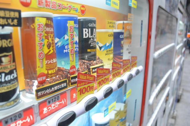 120円の缶コーヒーとともに100円のお買い得品が並ぶ自動販売機=2014年2月28日の朝日新聞