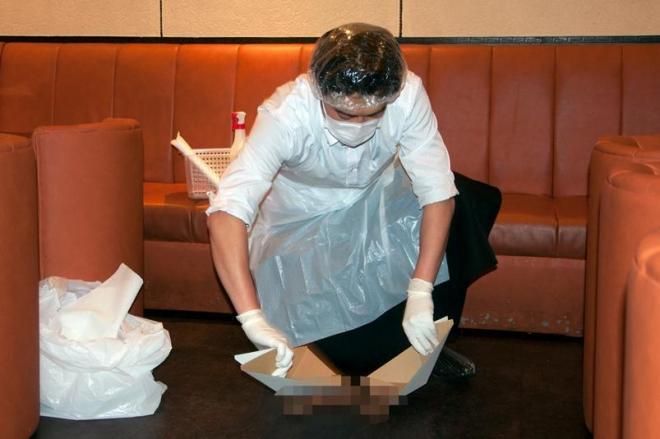汚物(※演習用の木片)の処理を実演するカラオケ店の店員。服につけないよう使い捨てエプロンで完全防備