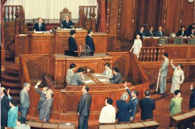 PKO協力法案をめぐる牛歩戦術。投票は朝になっても延々と続き、立ち止まったまま傍聴席の激励に手を振って答える議員たち=1992年6月6日