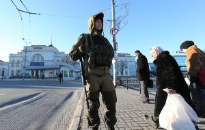 閉鎖しているドネウクライナ東部のツク駅の前で警備する銃を持った親ロシア派の兵士。到着したバスから降りた乗客が足早に通り過ぎた=2015年2月18日、ドネツク、葛谷晋吾撮影