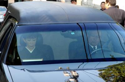 棺を乗せた車の助手席に座る、妻のうつみ宮土理さん=17日午前8時ごろ、東京都内の愛川欽也さんの自宅前