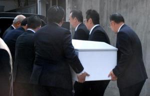 棺を車に乗せる男性たち=17日午前8時ごろ、東京都内の愛川欽也さんの自宅前