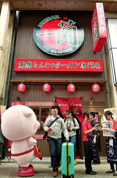 5階建てのラーメン店からスーツケースを手に出てくる外国人観光客=16日午後0時49分、大阪市中央区、竹花徹朗撮影