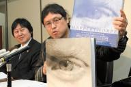 最高裁判決後の記者会見で、メイプルソープ写真集を手にする原告の浅井隆さん(右)と山下幸夫弁護士=2008年2月19日、東京・霞が関の司法記者クラブで