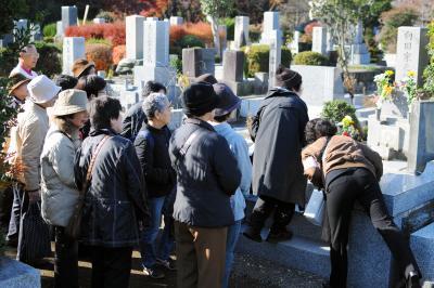 人気脚本家向田邦子さんのお墓の前でボランティアガイドの説明を聞く参加者=2010年12月1日、府中市の多磨霊園