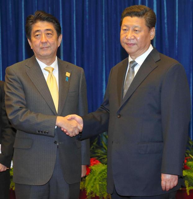 会談前に握手する習近平国家主席(右)と安倍晋三首相。習主席はほぼ無表情で、安倍首相も・・・=2014年11月10日、北京、代表撮影