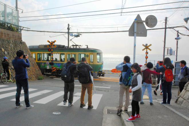 江ノ電・鎌倉高校前駅そばの踏切で写真を撮る観光客たち=2014年11月9日、鎌倉市腰越