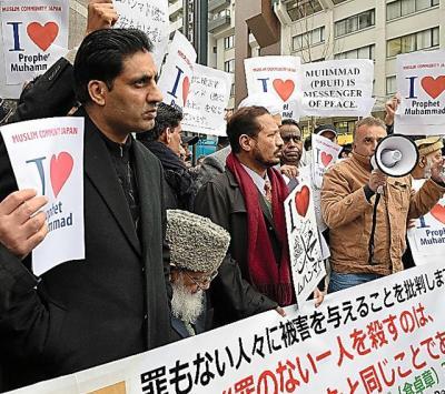 仏週刊新聞「シャルリー・エブド」などに載った風刺画をまとめた本を発行した「第三書館」の入るビルに向かって「宗教を侮辱するのはやめろ!」などと声をあげるパキスタン人ら=2015年2月14費、東京都新宿区、高橋友佳理撮影