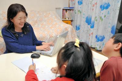 クラウドソーシングで働くフリーライター。リビングで宿題をする子供と一緒に執筆することも=2015年1月、東京都国分寺市