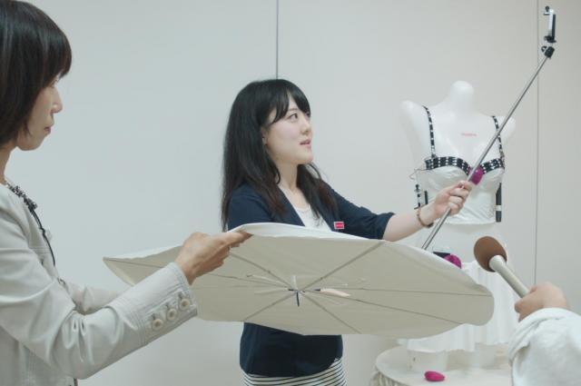 「レフ板」に照らされながら自撮り棒を操作する、トリンプ・インターナショナル・ジャパンの河村麻美さん。今回の開発を担当した