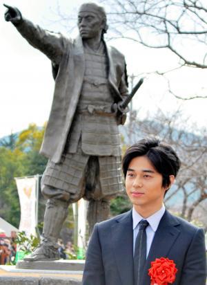 久坂玄瑞の銅像と玄瑞役を演じる東出昌大さん=2015年1月24日、萩市