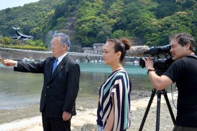 三軒一高町長(左)に取材する佐々木芽生監督(中央)。左奥にクジラをあしらったオブジェが見える=2015年4月27日、和歌山県太地町