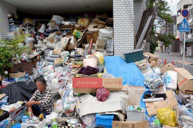 テレビ局の取材を受ける男性(左)。空き缶や段ボールなどのゴミが歩道にまであふれ、住宅の玄関はふさがっている(画像の一部を加工しています)=名古屋市中区、三上元撮影