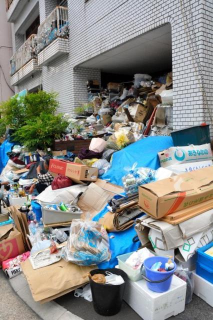 空き缶や段ボールなどのゴミが歩道にまであふれた男性(左側)の住宅。玄関はふさがり、2階のベランダにもごみが見える=名古屋市中区、三上元撮影
