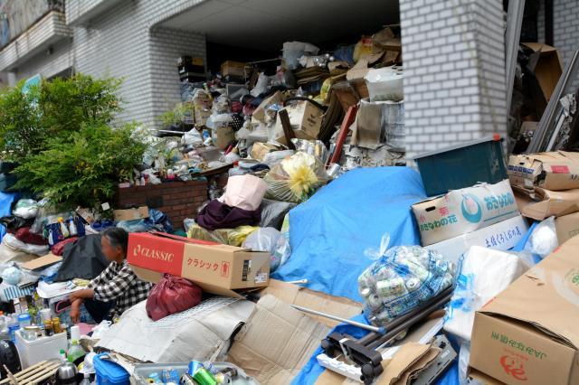 空き缶や段ボールなどのゴミが歩道にまであふれた男性(左)の住宅。玄関はふさがって入れない(画像は一部を加工しています)=名古屋市中区、三上元撮影